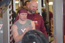 Blacksburg, Va., Sept. 6- PUSHING TEAMMATES: A key expectation of preferred walk-ons is the job of pushing starters. Here, Carroll cheers on his teammates completing a set of benchpress. Photo: Blayne Fink
