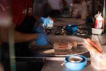 Blacksburg, Va., Feb. 26 - ROLL THEM UP: A worker finishes the rolled ice cream process. Using metal spatulas, the ice cream is scrapped off vertically to form a rolled look. Photo: Ricky Lam.