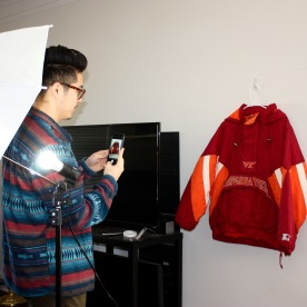 Blacksburg, Va. February 18 – Instagram Aesthetic: Tan takes a picture of a Virginia Tech windbreaker to put up on the Instagram page. He says he takes the pictures the same way with the same lighting every time to make sure the page looks clean. Photo: Maria Berkowitz