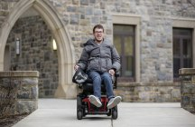 Blacksburg, Va., Feb. 19 — CRUISING TO CLASS: Trent Neely, a senior studying cinema, makes his way to class on his electric wheelchair. Photo: Loren Skinker.