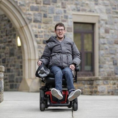 Blacksburg, Va., Feb. 19 — CRUISING TO CLASS: Trent Neely, a senior studying cinema, makes his way to class on his electric wheelchair. Photo: Loren Skinker.